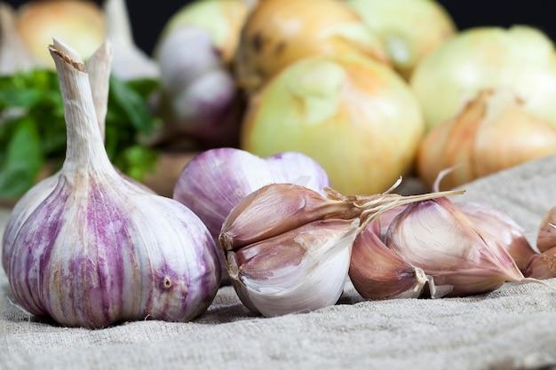 Légumes sur la table pendant la cuisson des gousses d'ail rouges mûres et des légumes et des épices au basilic vert sur une nappe en lin