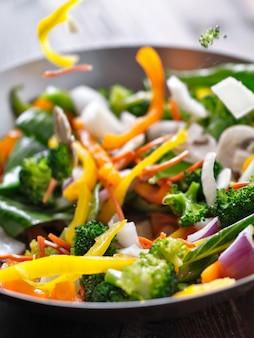 Légumes tombant dans un wok sauté