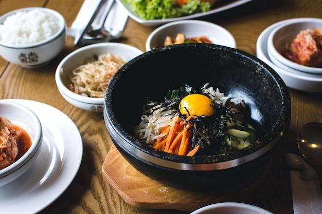 Légumes traditionnels coréens bibimbap avec jaune d'oeuf cru