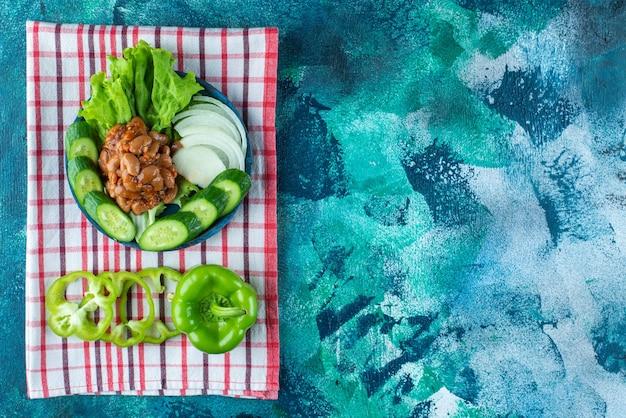 Légumes tranchés et fèves au lard sur une plaque en bois sur une serviette , sur la table bleue.