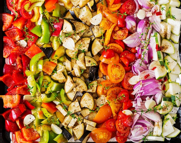 Légumes en tranches sur une plaque à pâtisserie préparée pour la cuisson.