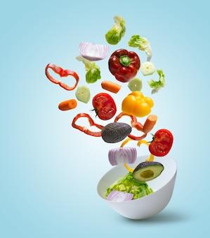 Légumes tranchés tombant dans un bol avec salade