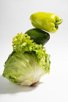 Légumes verts frais sur fond gris. équilibre alimentaire de la salade, du poivron et de l'avocat.vertical