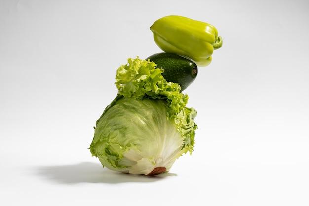 Légumes verts frais sur fond gris. équilibre alimentaire de la salade, du poivron et de l'avocat.