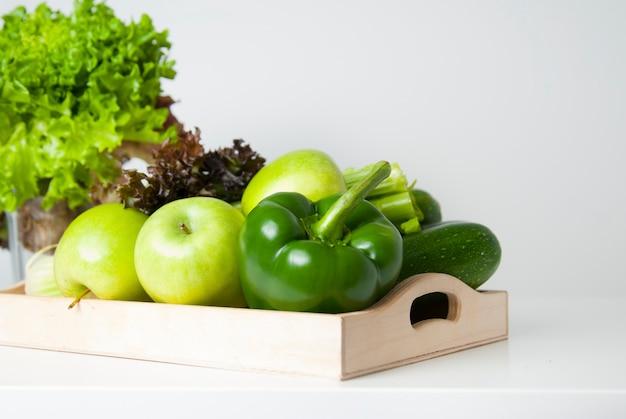 Légumes verts frais et fruits dans une boîte en bois.
