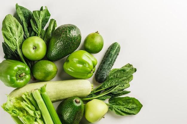 Légumes verts et fruits sur blanc