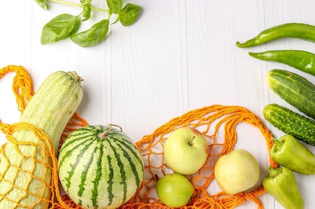 Légumes verts et fruits dans un sac en filet réutilisable orange sur une surface blanche de courgettes, concombres, poivrons, piments, pommes, poire, pastèque et basilic