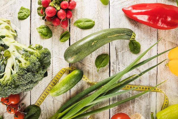 Légumes vifs et ruban à mesurer sur fond en bois