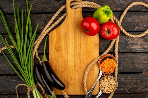 Légumes une vue de dessus de légumes mûrs comme les aubergines de tomates rouges et le poivron vert avec des haricots et des verts sur un bureau en bois rustique