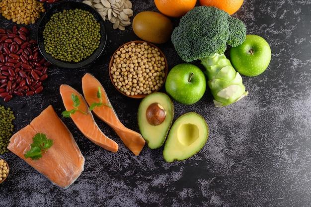 Légumineuses, brocoli, fruits et saumon placés sur un sol en ciment noir.