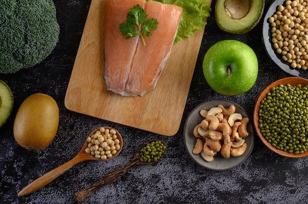 Légumineuses, fruits et morceaux de poisson saumon sur une planche à découper en bois.