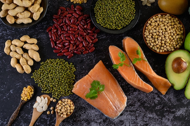 Légumineuses, fruits et saumon placés sur un sol en ciment noir.