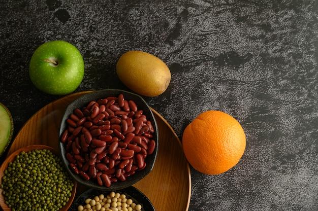 Légumineuses et fruits sur un sol en ciment noir.