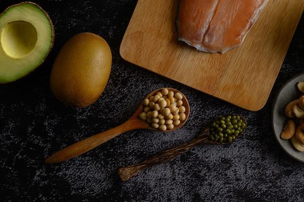 Légumineuses, morceaux de saumon et kiwi sur une surface de sol en ciment noir.