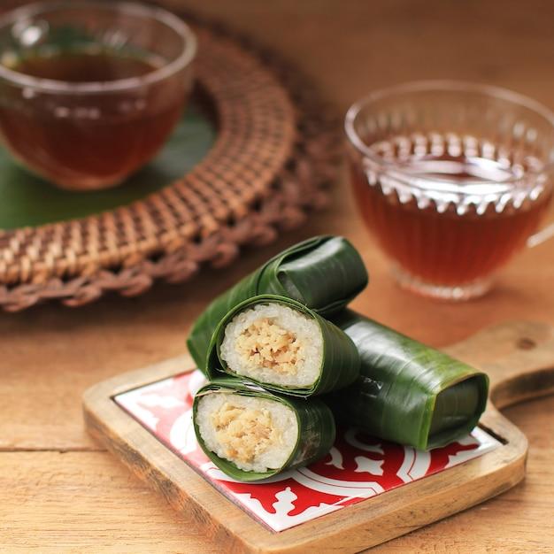 Lemper ayam servi avec du thé. lemper est une collation indonésienne à base de riz gluant rempli de poulet râpé assaisonné enveloppé dans une feuille de bananier, servi pour l'heure du thé
