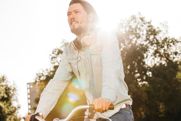 Lens flare tombant sur l'élégant jeune homme avec un casque autour du cou à bicyclette
