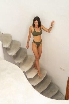 Lentement mais sûrement. portrait grandeur nature d'une jolie jeune femme aux cheveux noirs aux pieds nus et élancée en descendant les escaliers