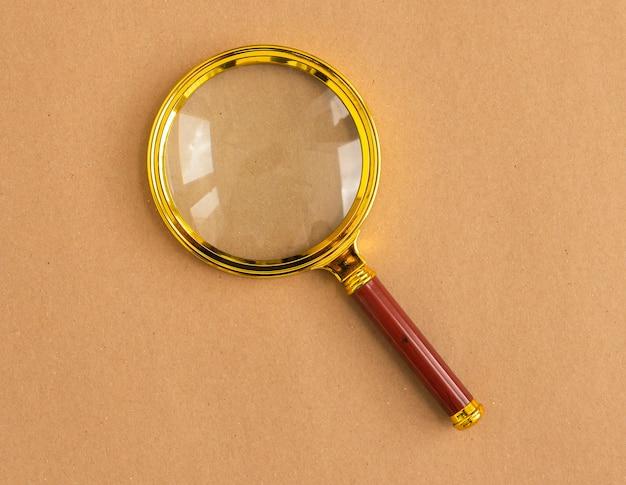 Lentille grossissante dorée sur carton artisanal. outil de recherche.