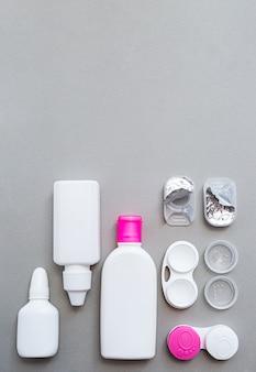 Lentilles de contact et accessoires à plat sur un motif gris
