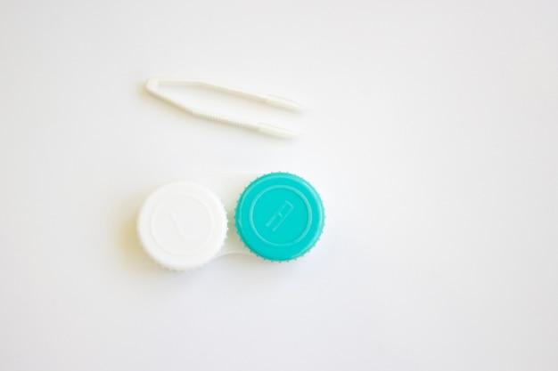 Lentilles de contact dans un contenant et une pince à lentilles