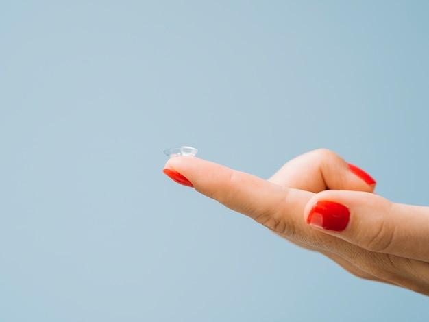 Lentilles de contact sur un doigt de femme