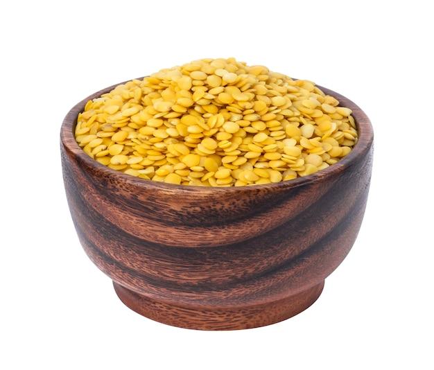 Lentilles jaunes dans un bol en bois isolé sur blanc
