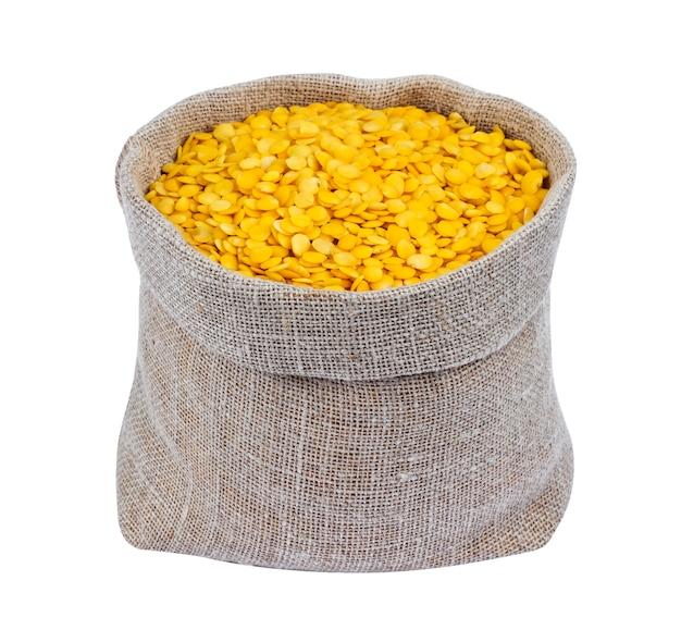 Lentilles jaunes dans un sac isolé sur fond blanc