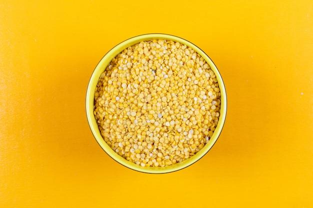 Lentilles jaunes à plat dans un bol jaune