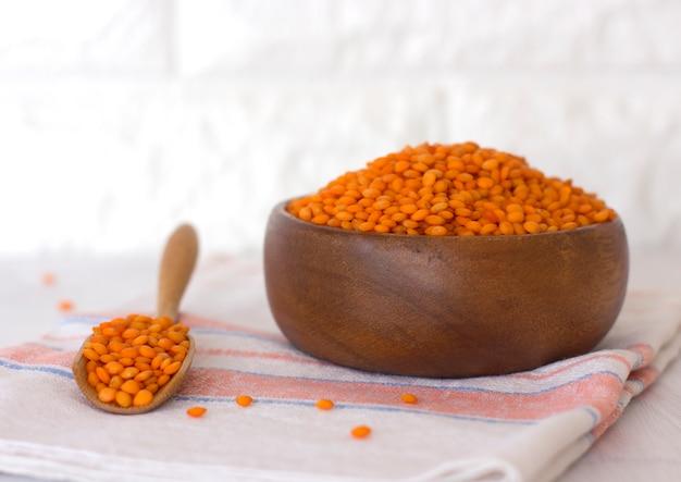 Lentilles rouges crues dans un bol en bois et cuillère sur une serviette en lin sur une table blanche