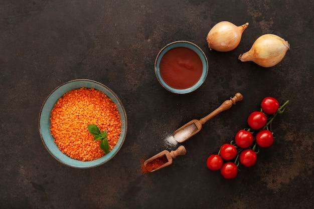 Lentilles rouges, tomates, oignons, pâte de tomates et épices, ingrédients pour la cuisson de la soupe à la crème