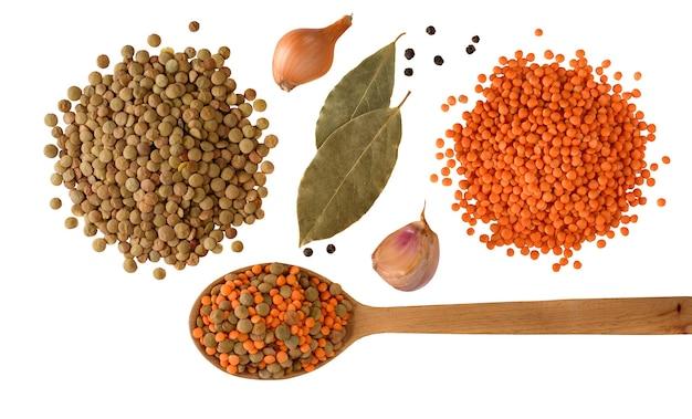 Lentilles rouges et vertes à l'oignon, à l'ail et aux épices avec une cuillère en bois isolée sur fond blanc. mode de vie sain. ingrédients de la soupe aux lentilles. mise à plat. vue de dessus.
