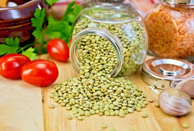 Lentilles vertes dans un bocal en verre, persil, ail, tomates, pot en argile, serviette sur fond de planches de bois