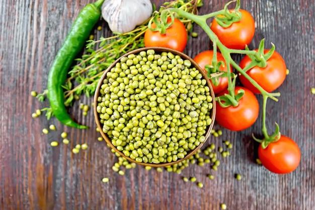 Lentilles vertes mung dans un bol, piments forts, ail, thym et tomates rouges sur fond de planche de bois d'en haut