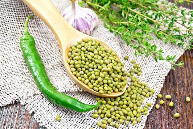 Lentilles vertes mung dans une cuillère avec des piments forts, de l'ail et du thym sur un sac sur un fond de planche de bois