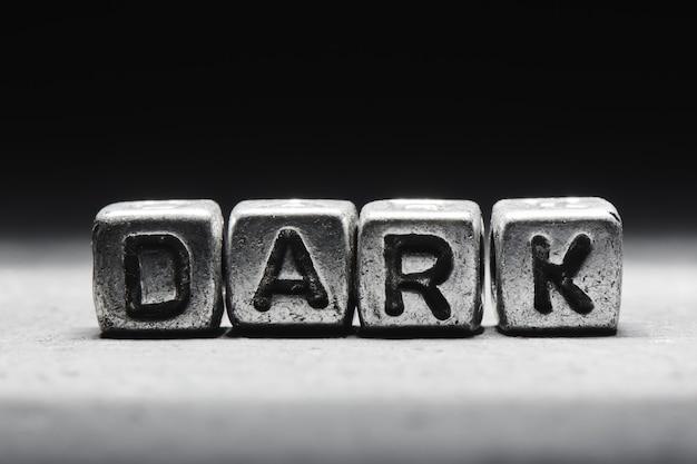 Lettrage concept sombre sur des cubes métalliques isolés sur fond noir