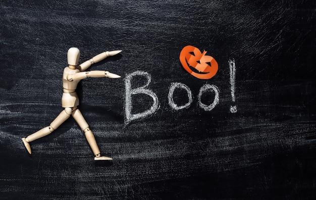 Lettrage à la craie boo! sur un tableau à craie avec un décor d'halloween. thème halloween