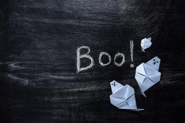 Lettrage à la craie boo! sur un tableau avec des fantômes en papier. thème halloween