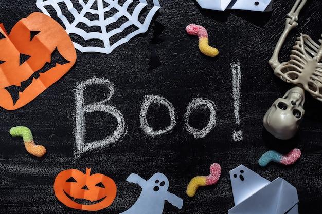 Lettrage à la craie boo! sur un tableau noir avec un décor et un squelette d'halloween faits à la main, des vers gommeux. thème halloween