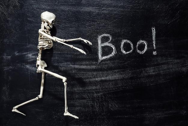 Lettrage à la craie boo! sur un tableau noir avec squelette. thème halloween