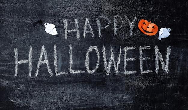 Lettrage à la craie happy halloween sur un tableau avec décor d'halloween