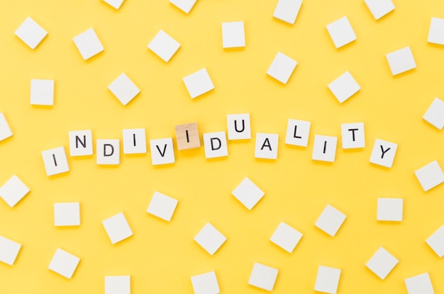 Lettrage d'individualité fait avec des cubes en bois sur fond jaune