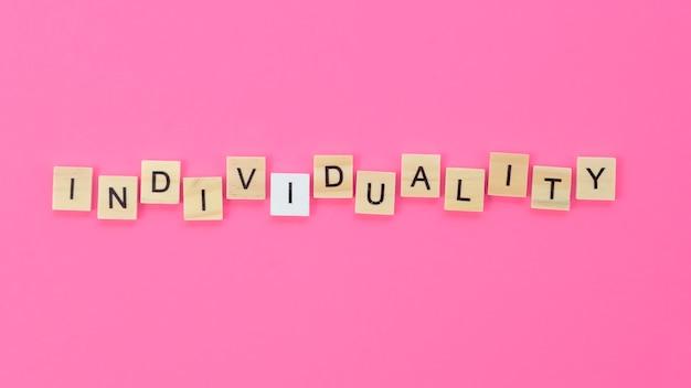 Lettrage d'individualité fait avec des cubes en bois sur fond rose