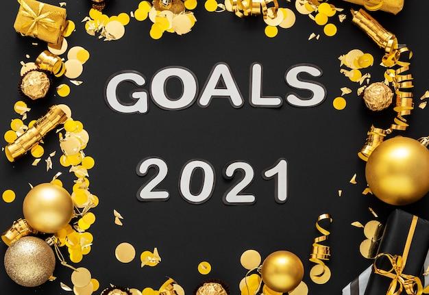 Lettrage des objectifs 2021 sur fond noir dans un cadre en or décor de fête de noël
