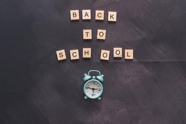 Lettrage de retour à l'école sur fond de craie texturée abstraite sur fond de tableau ou de tableau en graphite avec réveil. fond de mur sombre ou concept d'apprentissage. emplacement central