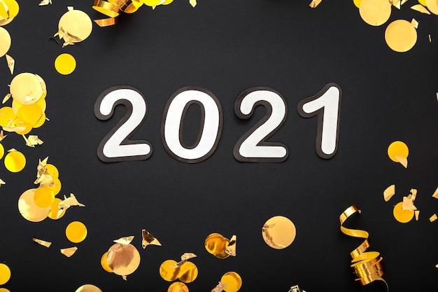Lettrage de texte 2021 sur fond noir avec décor de fête de noël or.
