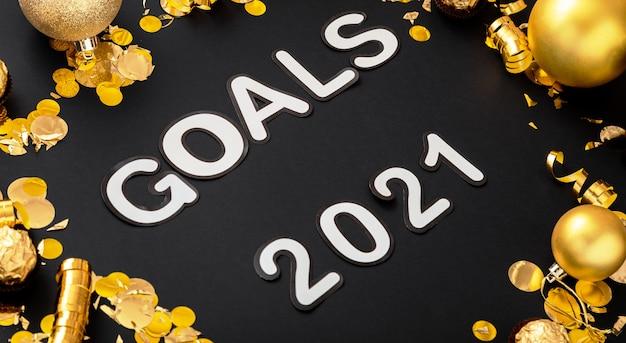 Lettrage de texte objectifs 2021 sur fond noir dans un cadre en or décor de fête de noël.