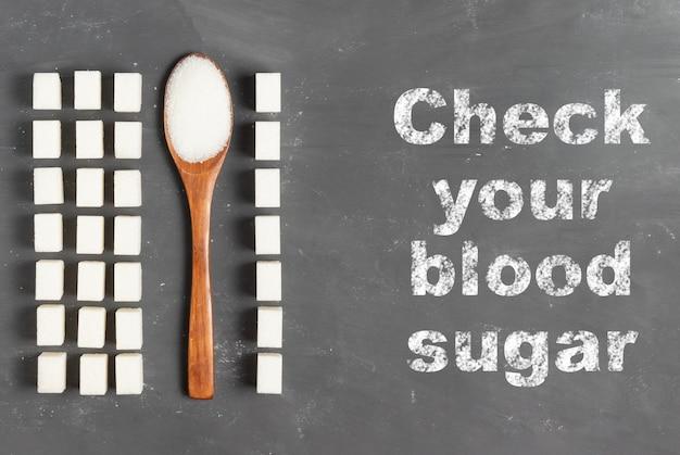 Lettrage vérifiez votre taux de sucre dans le sang avec de la craie sur fond gris