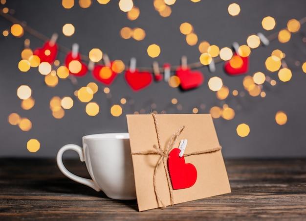 Lettre d'amour avec un coeur à côté d'une tasse sur fond de lumières, d'amour et de concept de la saint-valentin sur une table en bois