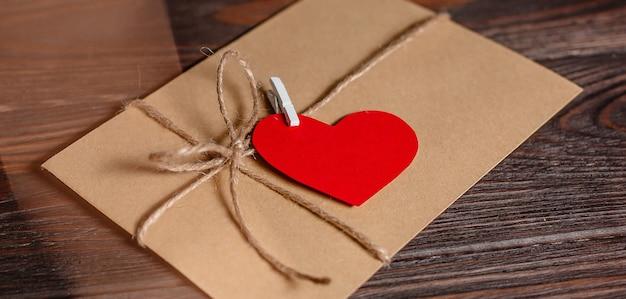 Lettre d'amour avec un coeur sur fond de lumières, d'amour et de concept de la saint-valentin sur une table en bois
