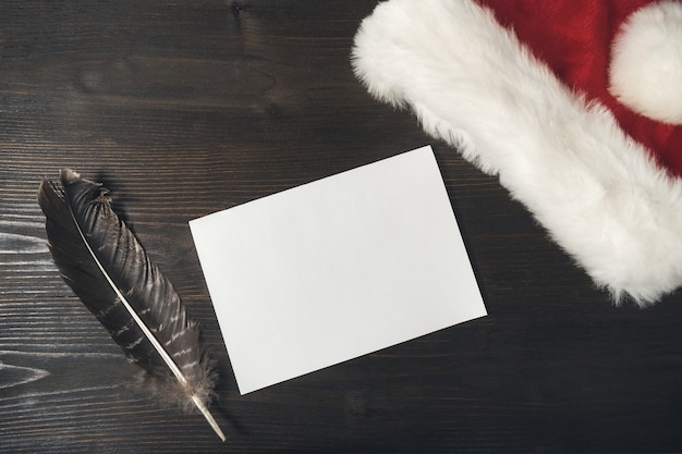 Lettre au père noël sur un bois. feuille vierge, stylo et chapeau. noël et nouvel an